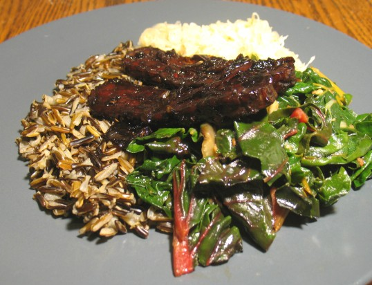 Glazed tempeh with greens, sauerkraut, and wild rice.